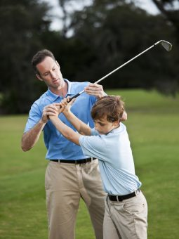 Golf instructor teaching boy (14 years) how to swing golf club, checking grip.  Main focus on hands.