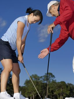 Golf pro teaching young female golfer on driving range.